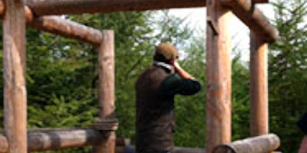 Mann in ländlicher Kleidung und Mütze Tontaubenschießen