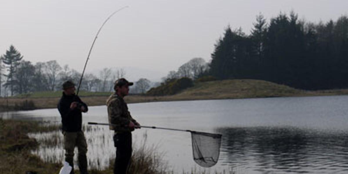 2 Angler, die einen Fisch mit einem Netz landen