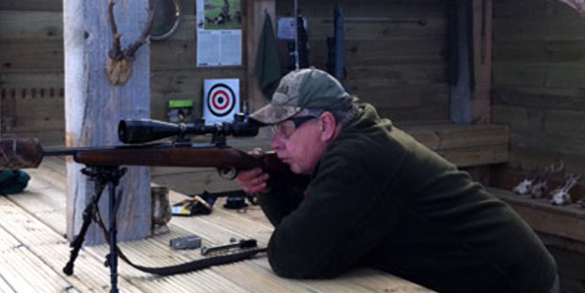 hombre en la tapa con el objetivo de rifle de aire