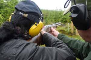 clay pigeon shooter with cap and yellow ear defenders receiving instruction