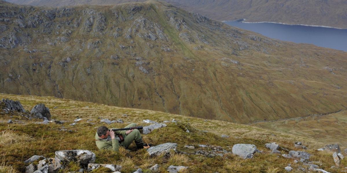 stalker using telescope on hillside