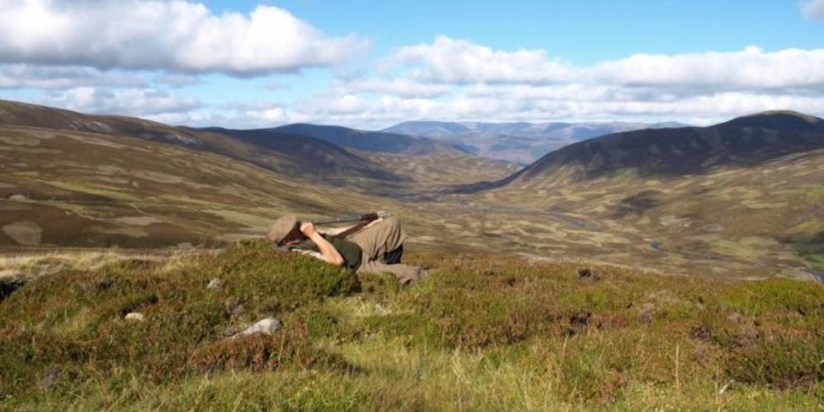 Schottischer Hang mit blauem Himmel und Stalker, der für Hirsche ausspioniert
