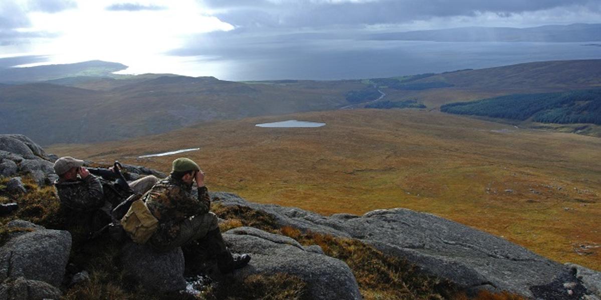 2 acosadores uno con binoculares en busca de ciervos
