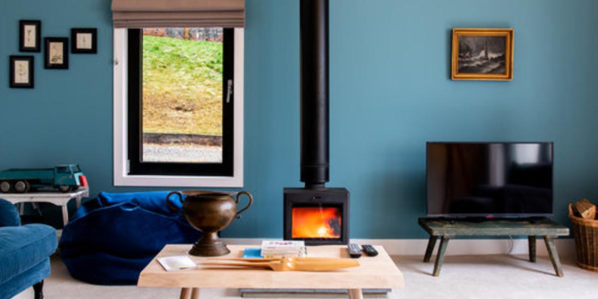 Estufa de leña en salón pintado de azul con ventana grande