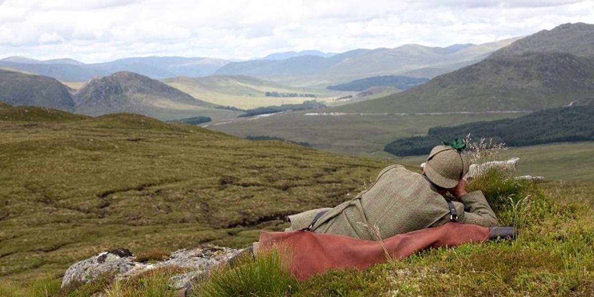 Scottish highland deer stalker lying on grassy hillside