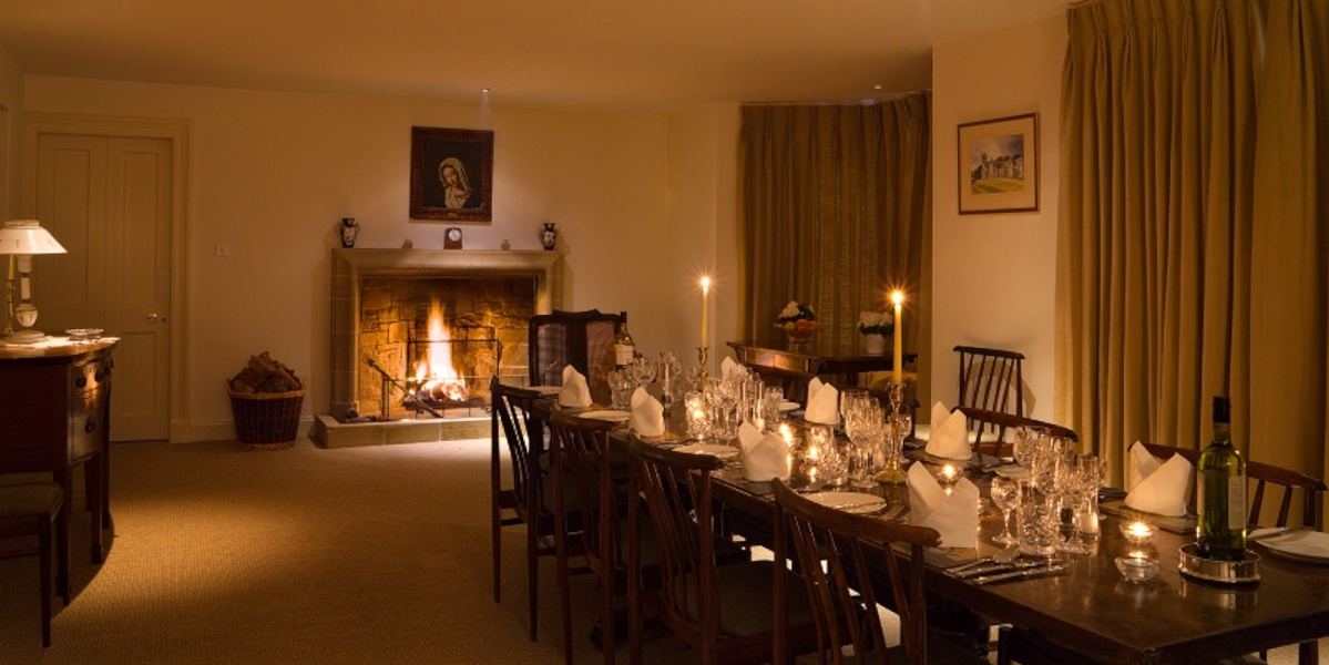 contry house dining room with lit open fire