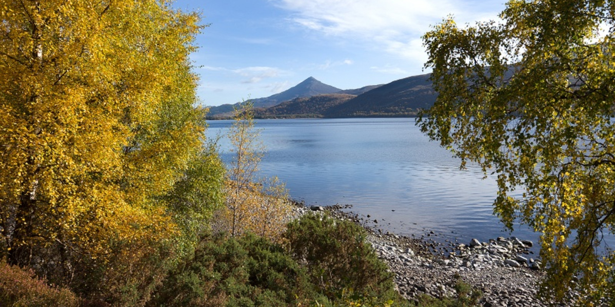 Scottish loch with mountain and blue sky