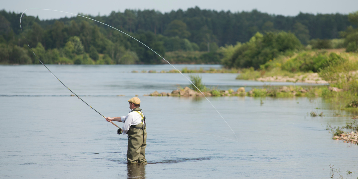 man fly fishing for atlantic salmon on river