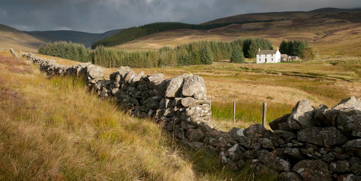 whitewashed highland lodge in Scottish highland landscape