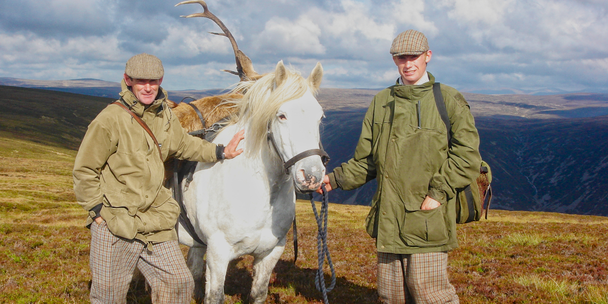 2 men with Scottish hill pony carry a stag