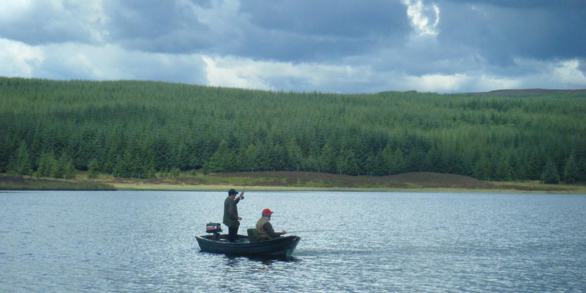 two fishermen in boat on loch