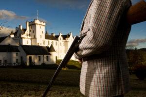 uomo in tweed con fucile da caccia fuori dal castello scozzese