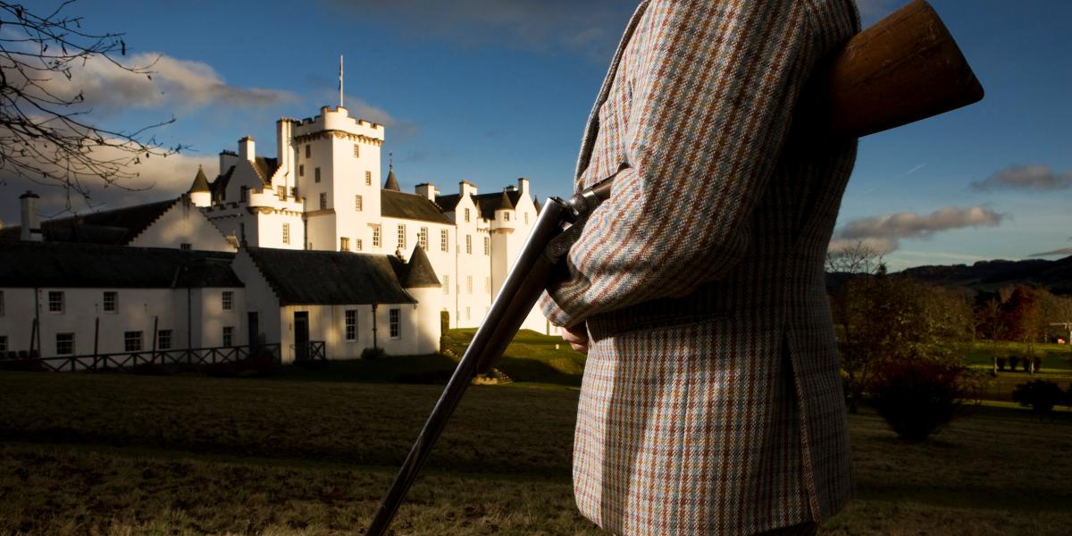 man in tweed with shotgun outside Scottish castle