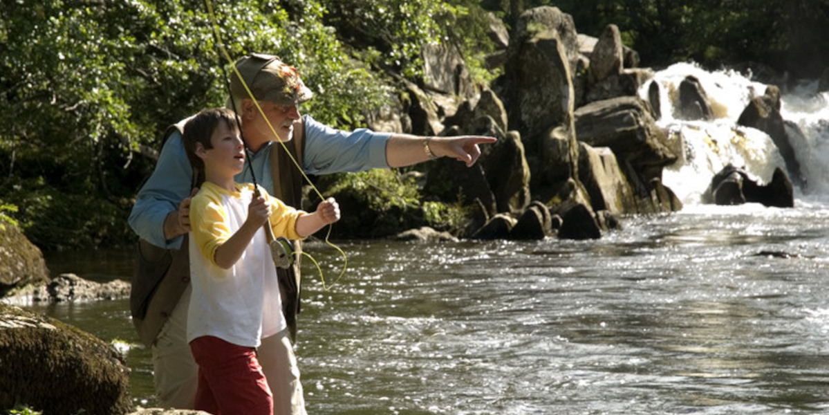 boy being taught to fly fish by ghillie on rocky stream