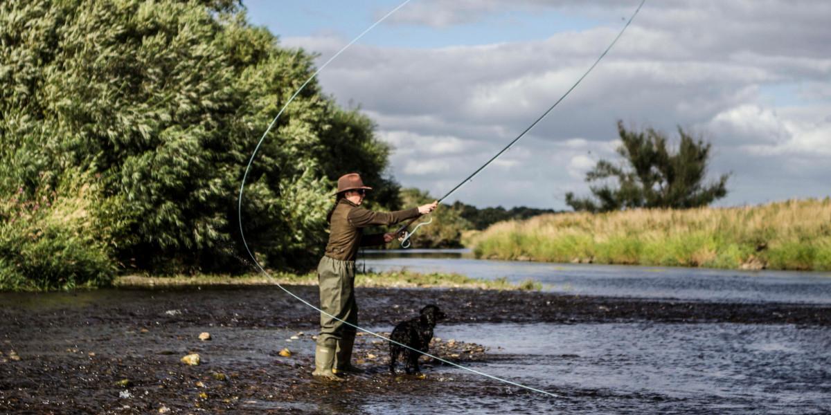 girl fishing and black dog