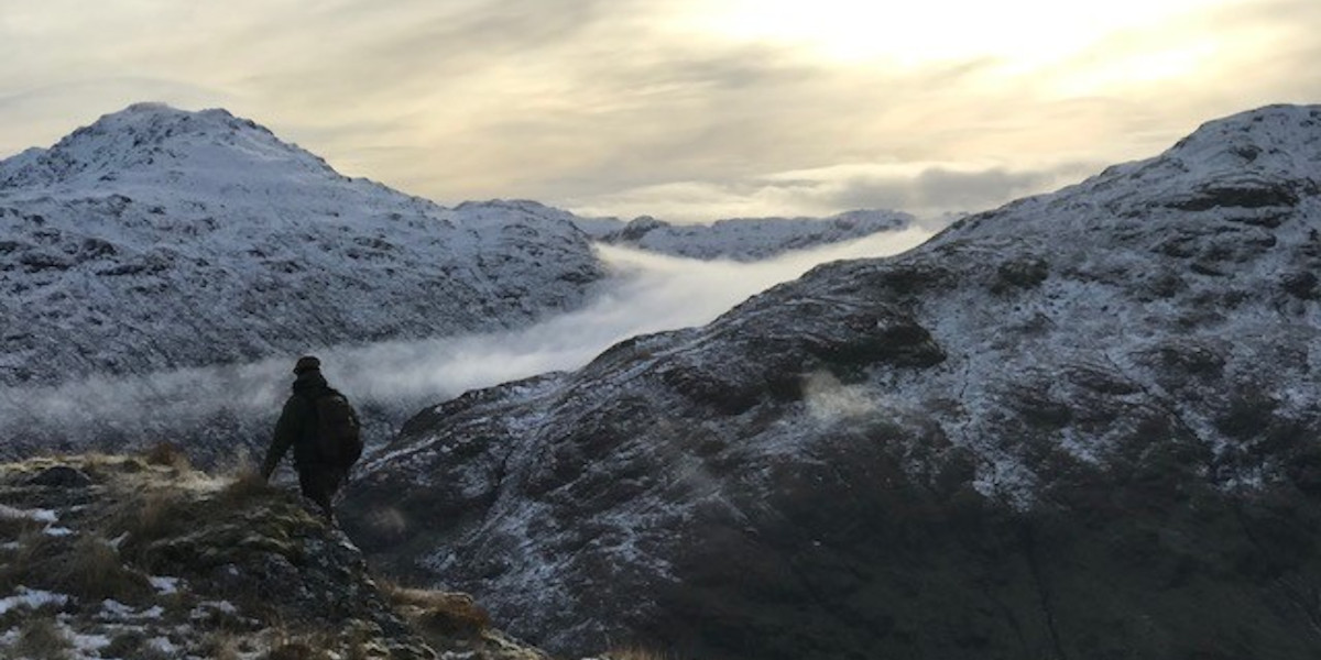 stalker on Scottish mountain with snow and mist