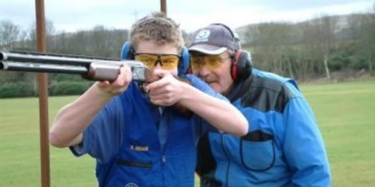 Schrotflintentrainer und Schüler tragen Blau und richten einen Schuss aus