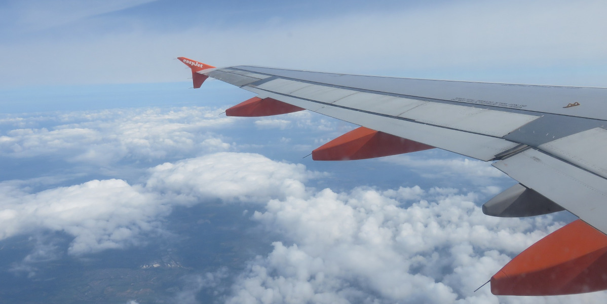grey and orange aircraft wing in flight