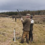 two men with shotguns in the field