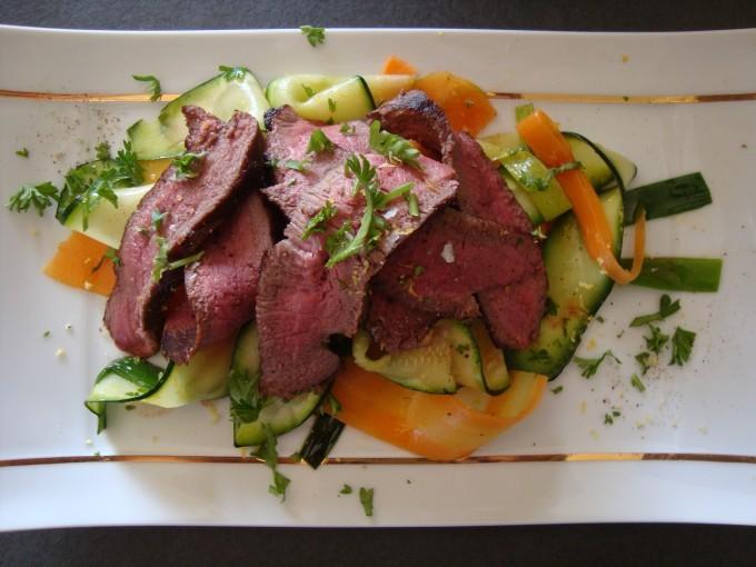 tallrik med skivat hjortkött och grönsaker
