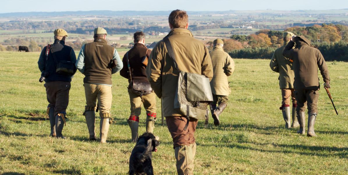 Rückansicht einer Gruppe von Männern mit Schrotflinten und einem Hund