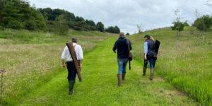vista posteriore di 3 persone con fucili da caccia