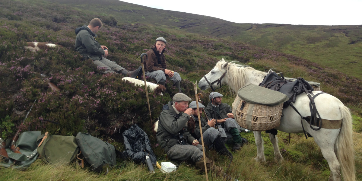 Männer und Garron Pony am Hang