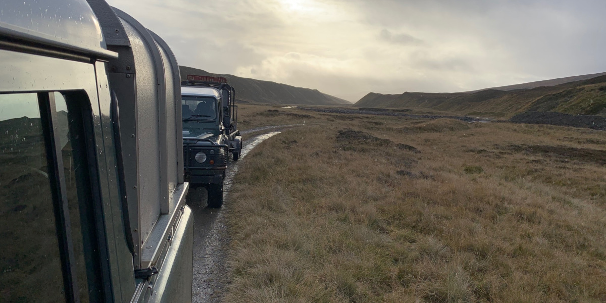 convoy of Land Rovers in a moorland landscape